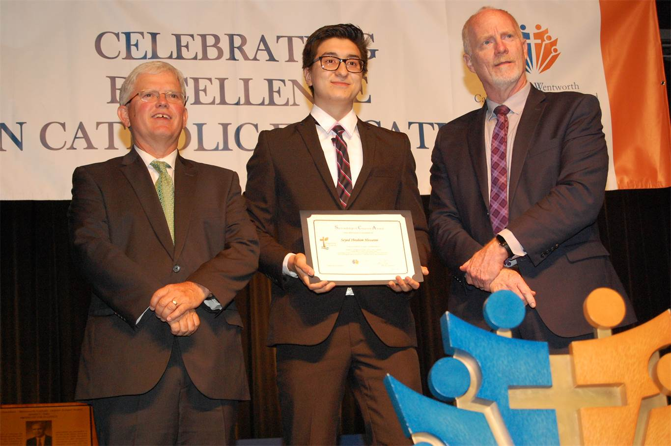 Chairperson Patrick Daly, left, and Director of Education David Hansen present Seyed Ibrahim Hosseini from Cardinal Newman CSS with the Board's Stewardship of Creation Award for his work to promote a more environmentally sustainable school community.
